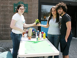 Roarie Borg (left), vice president of P.E.A.C.E., sells flowers outside Hillwood Commons to promote earth-friendly habits.